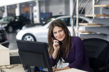 Woman on phone at desk in car dealership