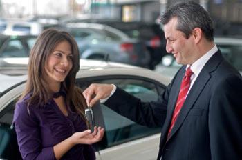 Salesman handing keys to woman